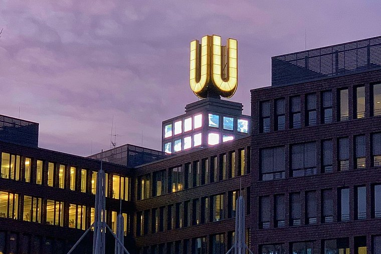 Dortmunder U in the dusk. The big U on top is illuminated and the sky is coloured violet.