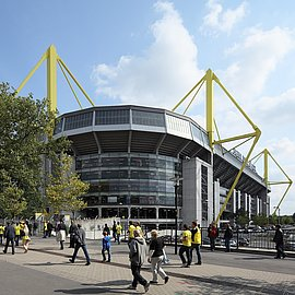 Fans walking in front of Signal Iduna Park to attend the football match.