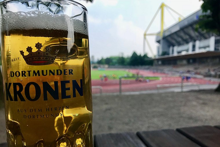 A glass with the inscription Dortmunder Kronen. In the background, the stadium Rote Erde and the stadium Signal Iduna Park are slightly blurred.