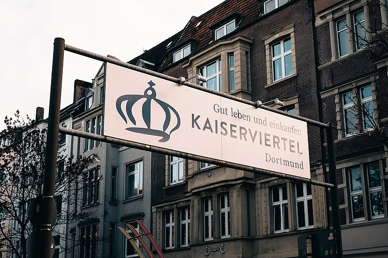 "Big street sign saying: Live and shop well at the ""Kaiser""-quarter in Dortmund"