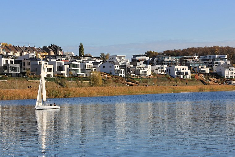 A small sailboat lies on the PHOENIX See lake. The sun is shining, bright blue sky. In the background, the new buildings can be seen.