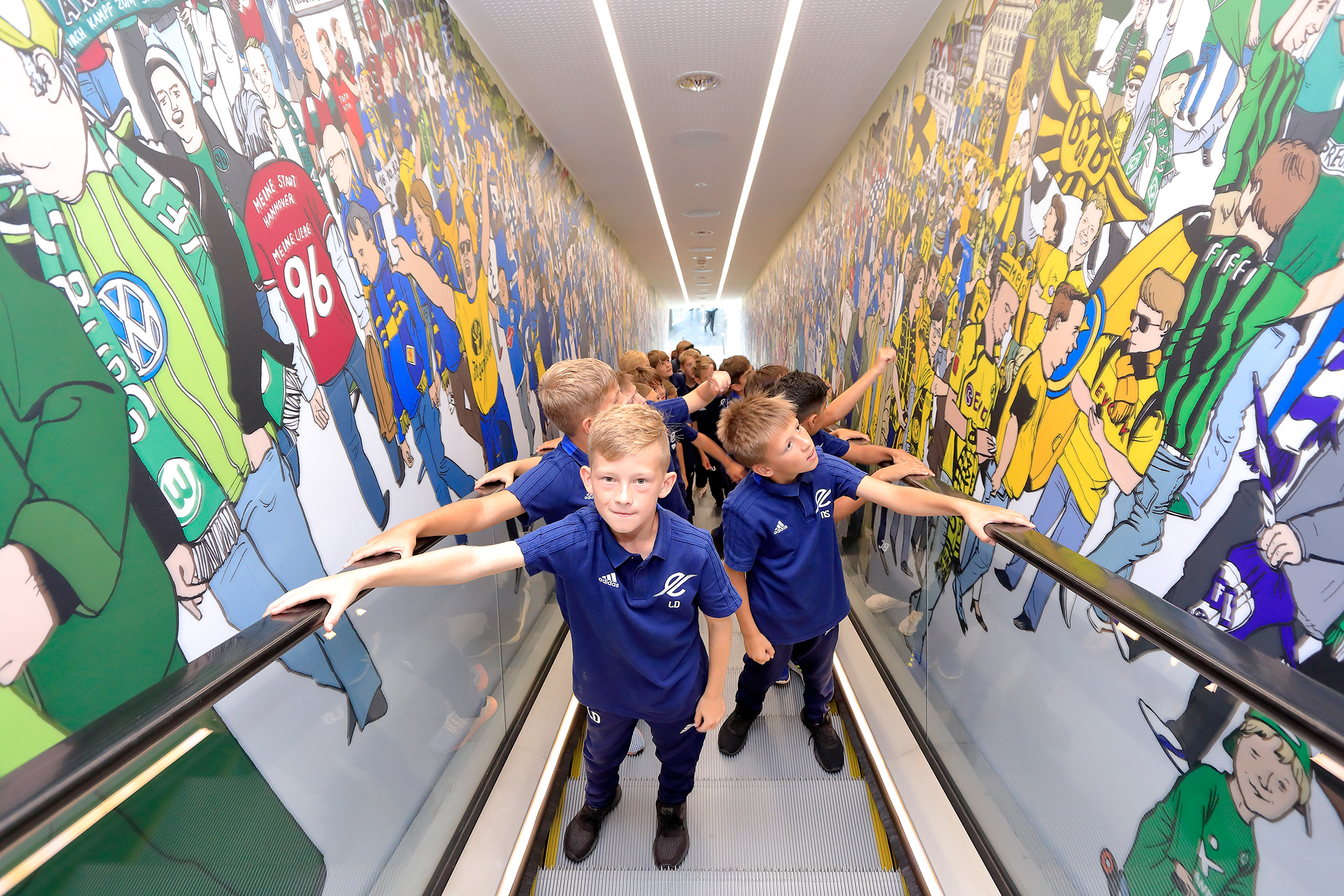 A youth team is taking the escalator in the German Football Museum.